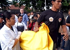 Indonesian paramedics carry the body of a blast victim
