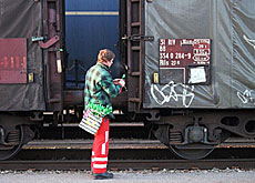 A railway employee checks a freight train at a goods station on the north-south axis