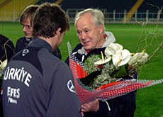 A Turkish player hands Kuhn a bunch of flowers to apologise for the hostile reception