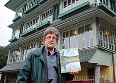 "Roland Flückiger, with his book, ""Hotel Palaces"", in front of the historic ""Dampschiff"" restaurant in Thun"