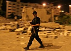 A Palestinian policeman patrols Gaza City after a missile strike at the Islamic University