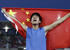 China's Liu Xiang celebrates his new world record of 12.88 seconds in the men's 110m hurdles