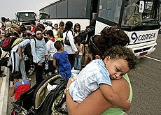 Buses take families to a port in northern Beirut from where they are evacuated