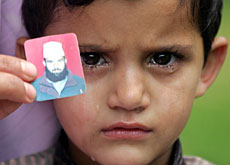 A Kashmiri boy holds up a photo of his missing father