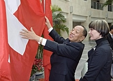 Micheline Calmy-Rey (right) tells Li Zhaoxing about the history and design of the Swiss flag