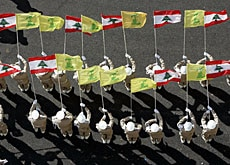 Hezbollah honour guards hold Lebanese and yellow Hezbollah flags during a recent rally in Beirut