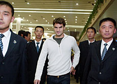 Federer surrounded by security as he arrives at the airport iin Shanghai