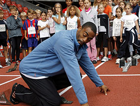 Sprinter Tyson Gay shows children how training is really done before a track meeting in Zurich