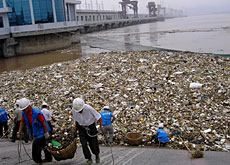 Workers clear waste at a Yangtze dam after a flood
