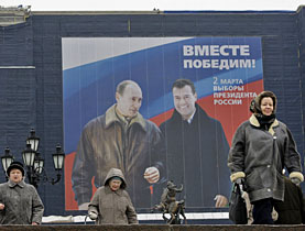 Russians walk under a giant election poster depicting President Vladimir Putin, left, and presidential candidate Dmitry Medvedev in Moscow