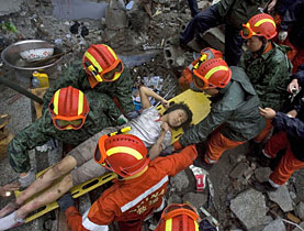 Rescue workers pull a girl out from under the rubble of a collapsed school in Sichuan