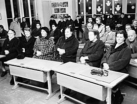 """برلمان منعقد في أحد الفصول الدراسية، في شهر يناير 1969، المجلس التشريعي لـ """"مامليسفيل Mümliswil"""" إحدى البلديات التابعة لكانتون سولوتورن، حيث يجري التصويت ضد مشروع حقل يخصص لتدرّب الجيش."""