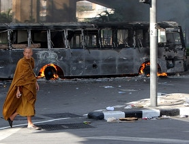 A Buddhist monk passes a burnt-out bus set alight by anti-government protesters in Bangkok on Monday