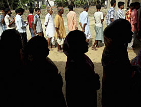 Swiss bankers? Indian villagers queue outside a polling booth at a village in Khejuri, 165km southwest of Calcutta
