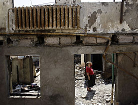 A woman surveys the remains of her house in Tskhinvali, regional capital of Georgia's break-away province of South Ossetia