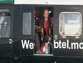 What goes up: Yves Rossy kneels in the doorway of a rescue helicopter after ditching in the sea