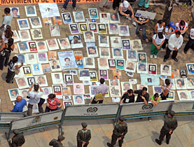Human rights activists display photos of victims of Colombia's political violence in Medellin