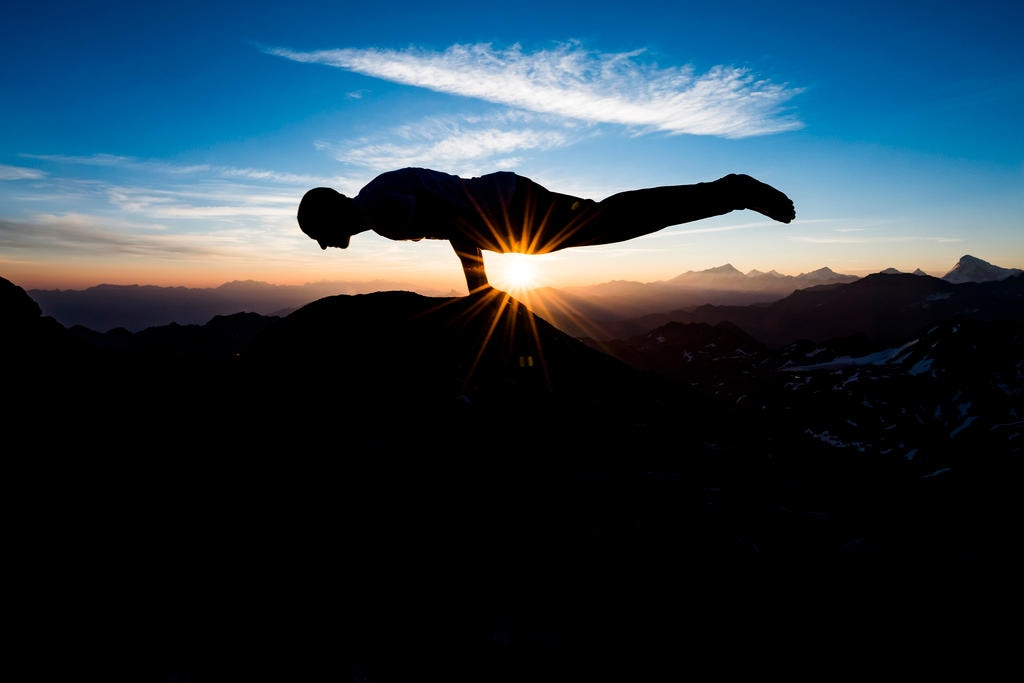 Silhouette of man practicing yoga at sunrise