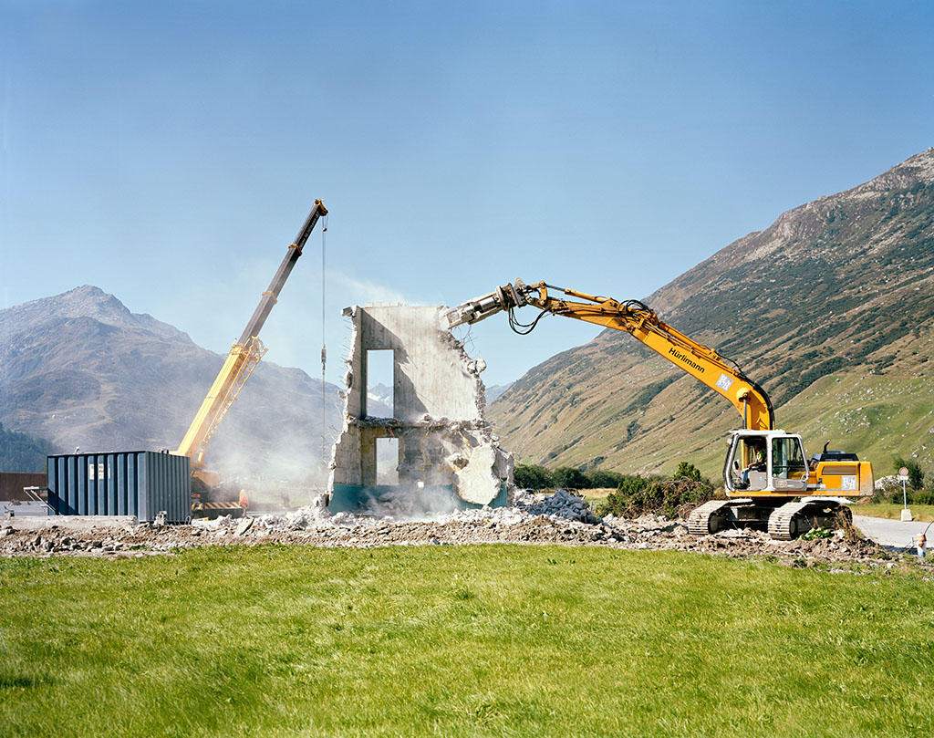 An excavator demolishing a house