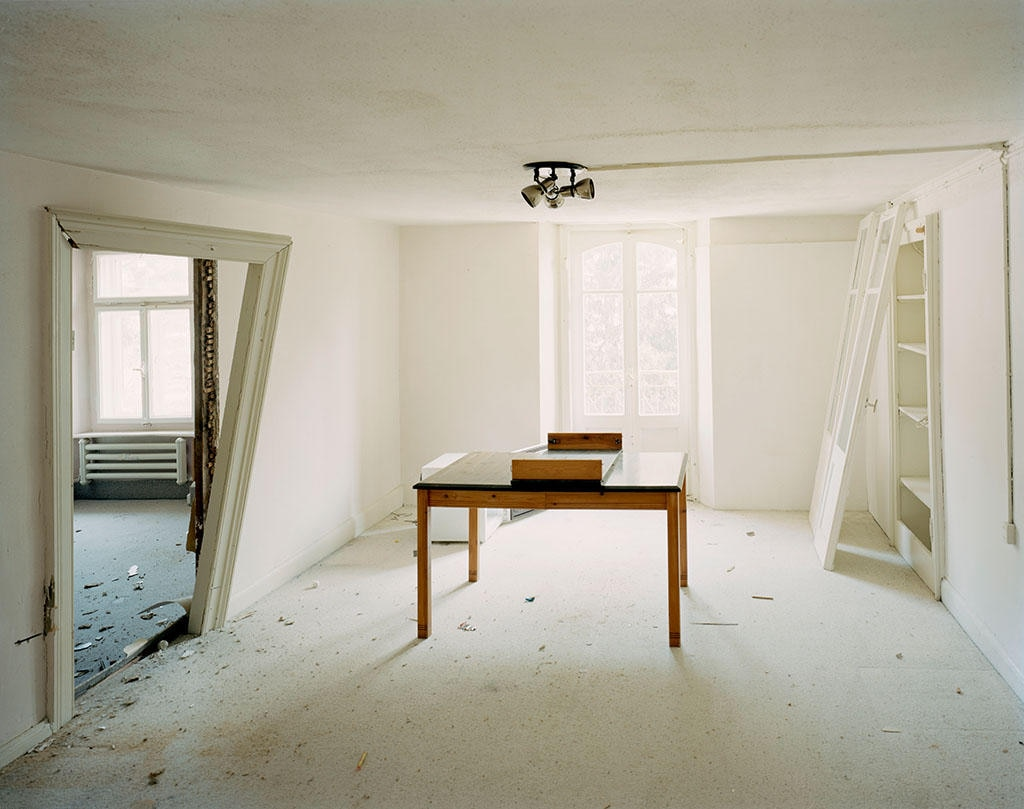 A room that has been partly demolished, a table stands in the middle.