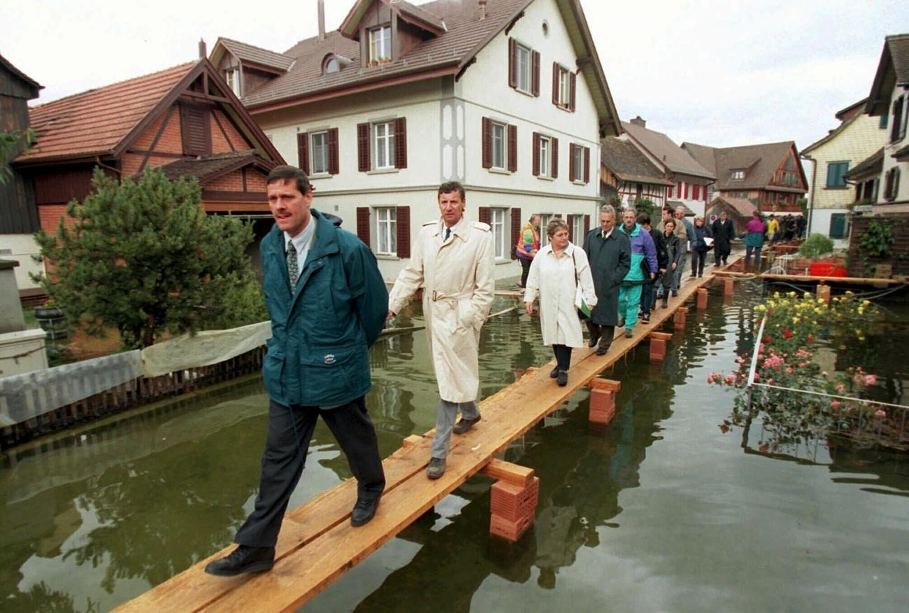 Roland Eberle, Philipp Staehelin, Vreni Schawalder and Hermann Lei walking on planks over flooded Thurgau