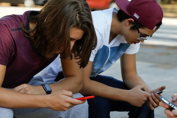 Drei Jugendliche starren auf ihr Handy.