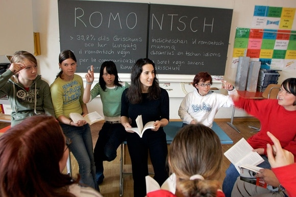 Kinder und eine Lehrerin in einem Klassenraum. An der Wandtafel stehen Sätze in Rätoromanisch.