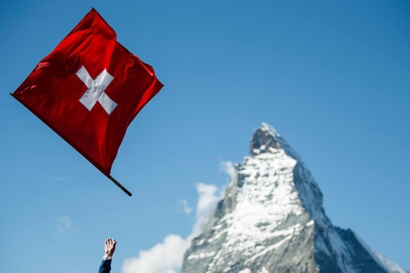 A Swiss flag is thrown in the air with the Matterhorn in the background
