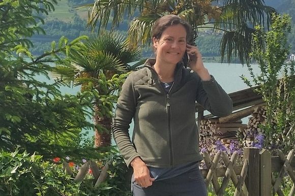 Alexandra Dufresne making a phone call in Switzerland, surrounded by trees and flowers.