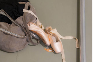 a apir of ballet shoes and a hand bag and a plaster