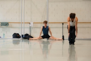two male dancers warming up