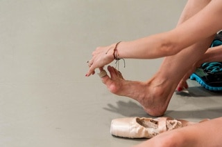 a dancer tending to her feet with plasters