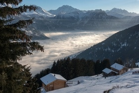 Three chalets overlook a cloud filled valley on a snowy hillside