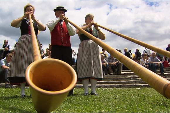 Two women and one man playing the alphorn.