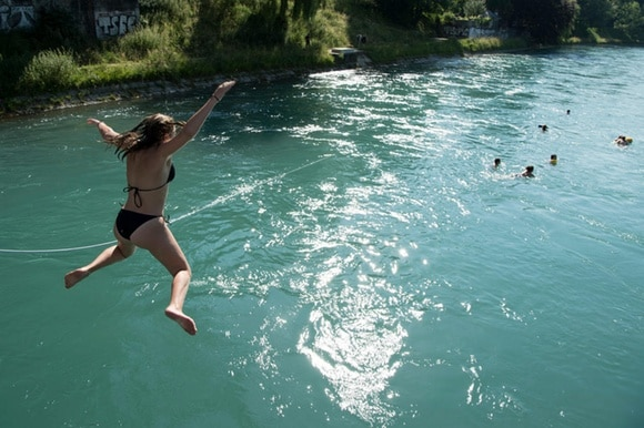 A woman in swimsuit jumps into a river to join other swimmers