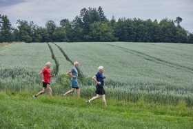 Three old age pensioners jogging in a field