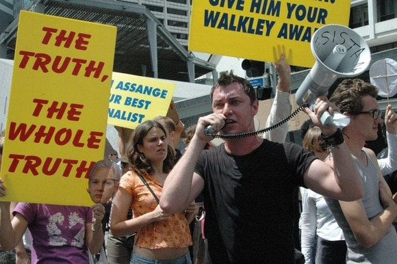 A man speaks into a megaphone amidst a crowd holding banners demanding truth