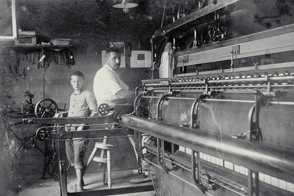 Black and white photo of a girl between two automatic looms
