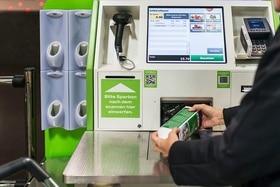 مستهلك يُمرر مشترياته على جهاز الخدمة الذاتية لإحتساب أسعار المشتريات