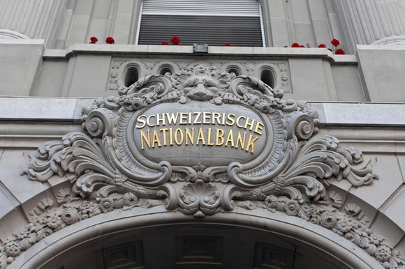 A gold lettered sign, framed by ornate masonry, reads Schweizerische Nationalbank