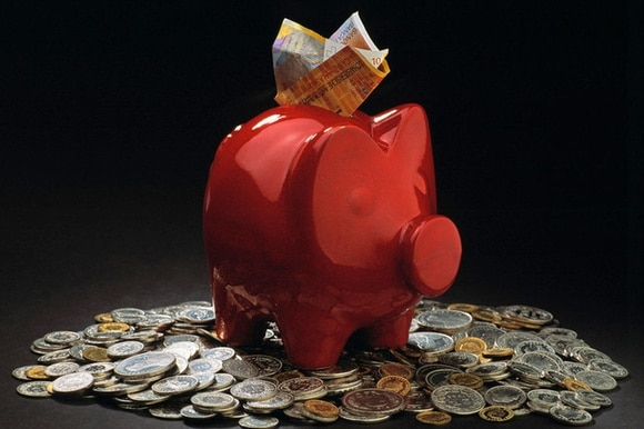 A red piggybank with notes sticking from the top sits on a pile of coins