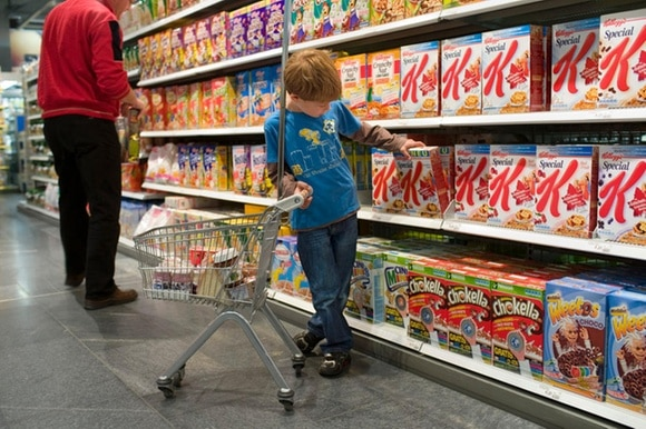 Boy taking package of cereals from a shelf in a supermarket