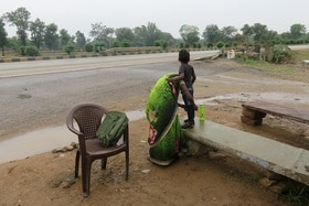 Boy stands on stone bench, mother bends over him.