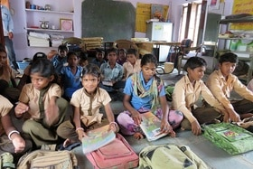 children sit in a school class with their school bags