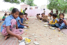 children eating lunch outside school