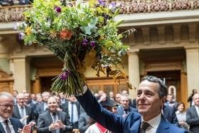 رجل يحمل باقة زهور ويوجه التحية للمواطنين