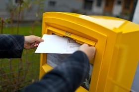 Yellow letterbox and somebody posting a letter