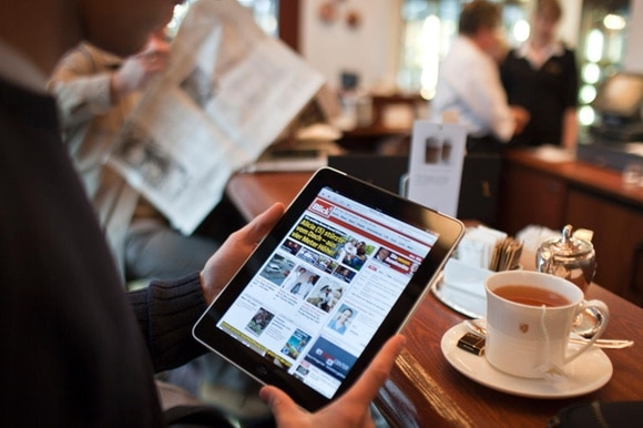 Man holding iPad, reading news, in a cafe