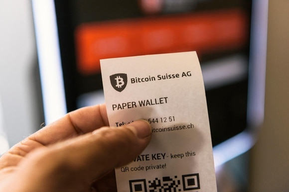 A hand holds a paper receipt for bitcoins