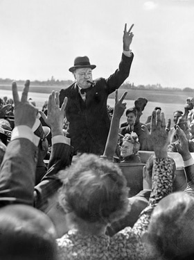 Winston Churchill gives the victory salute to a crowd